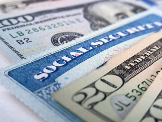 A Social Security card laying between $100 and $20 bills.