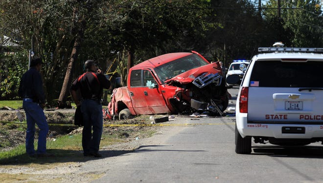 Police respond to the scene after a driver struck and killed two children and injured another as they walked to school Thursday, October 30, 2014, on Martin Street in Breaux Bridge, La.