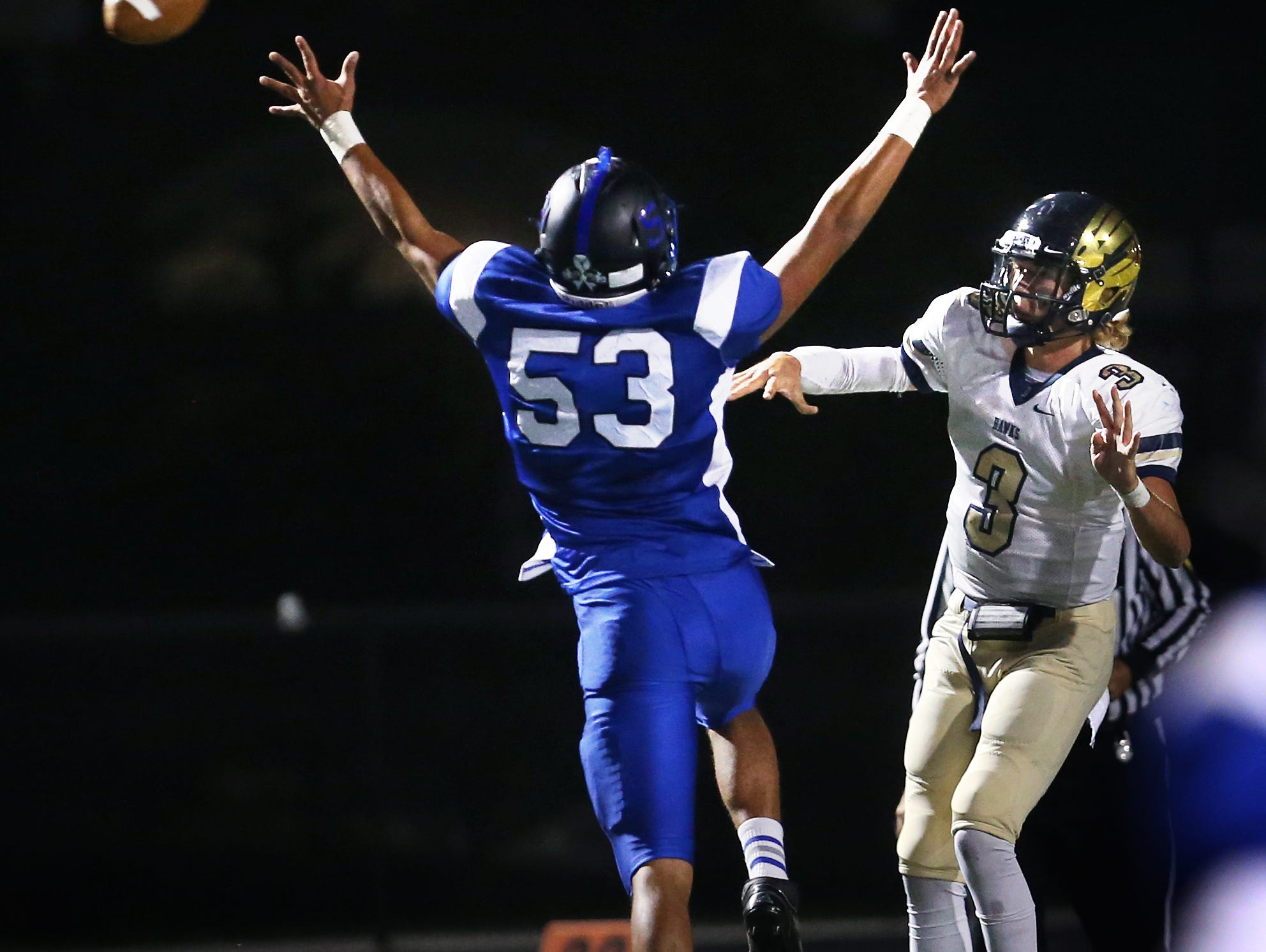 Decatur Central High School quarterback Tommy Stevens throws one of his passes on his 65-yard come-from-behind game-winning drive despite a valiant defensive effort from Franklin Grizzly Cub defender Tyler Hendricks at Franklin on Friday, October 17, 2014. The Hawks scored with 15.7 seconds left and came away with a hard-earned 27-23 victory over the Grizzly Cubs. (This was not the touchdown pass).