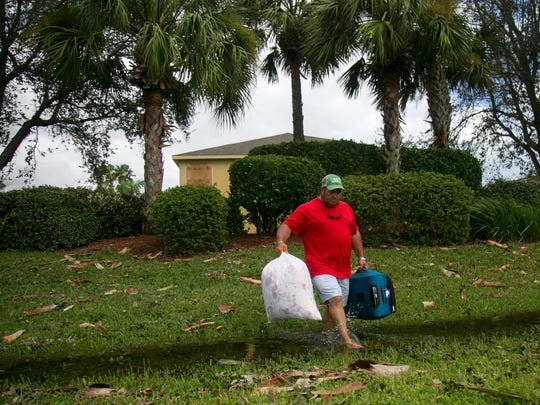 Mark Sanders brings clothes and bedding from his home in Cypress Cay in Gateway on Monday. The neighborhood roads are under water, but Sanders said his home was not flooded though.