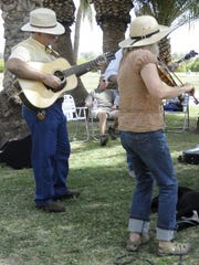 A group of musicians plays in an impromptu jam at the 2012 Glendale Folk and Heritage Festival at Sahuaro Ranch Park in Glendale.