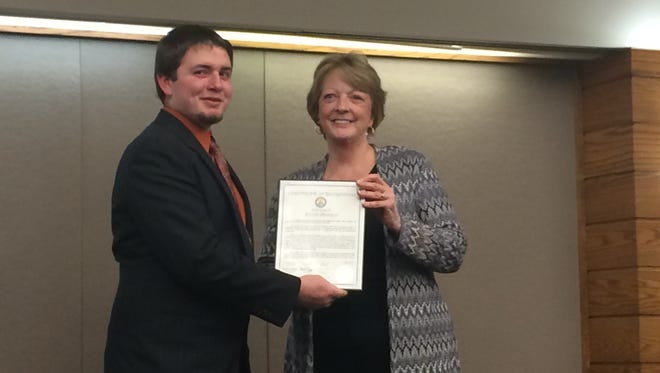 Livingston County 4-H Key Club Award winner Kevin Pentico accepts a certificate of recognition from county Board of Commissioners chairwoman Kate Lawrence.