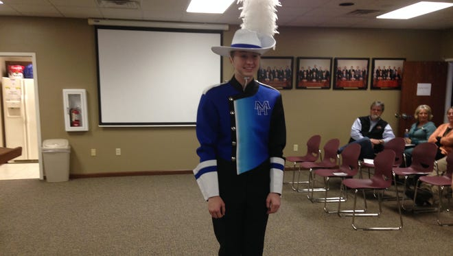 A Mountain Home student shows off a new band uniform during a school board meeting Thursday, Feb. 18, 2016. The board voted unanimously to accept a bid for high school band uniforms.