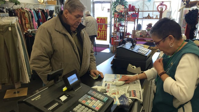 Volunteer Carmen Sowinski rings up purchases for Snow Hill resident Rob Hall. Sowinski has been volunteering at the shop for eight years and says chatting with regulars, like Hall, is her favorite part of the job.