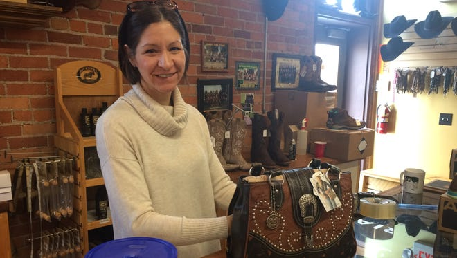 Howell Western Wear owner Lynn Elberson demonstrates how to use a concealed carry purse.