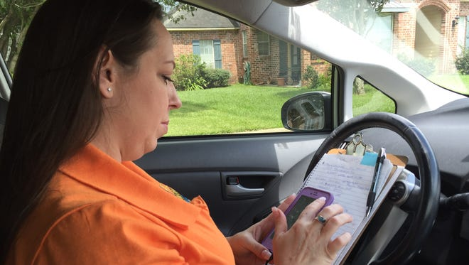 Osh Leveque-Perkins uses her phone GPS Tuesday to find the homes of people using Takeout Express services to donate to flood victims.
