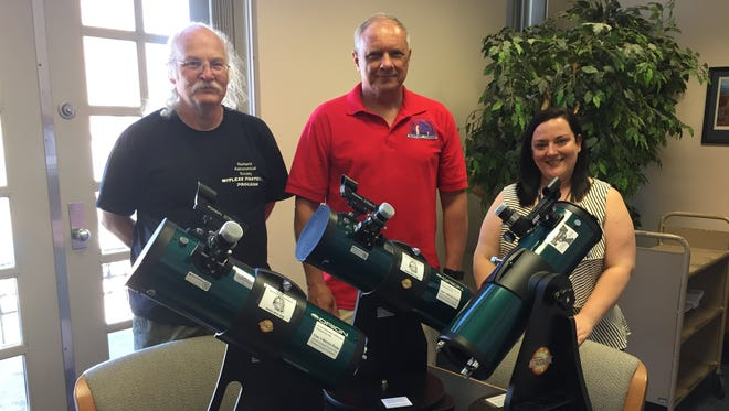Dan Everly and Tim Jankowski from the Richland Astronomical Society presented three telescopes to Mary Frankenfield of Mansfield Richland County Public Library Tuesday.