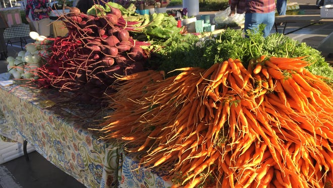 Carrots and radishes in the early morning sun at the Tallahassee Farmers Market at Market Square.
