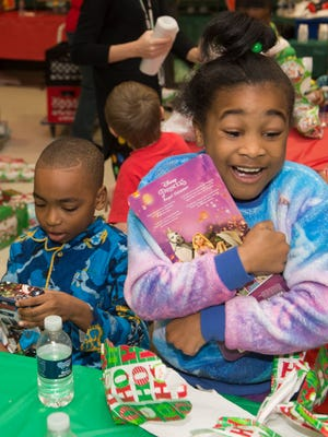 """First graders Caleb Robinson, left and Tyiea Browen, right, open gifts at David Hicks Elementary School in Inkster on Friday, Dec. 23, 2016 during a school party called """"The Miracle on Helen Street."""""""
