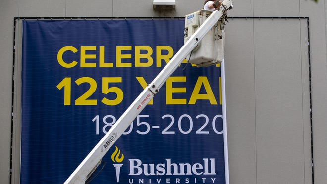 Fast Signs workers Will Hooker, top, and Dennis Hyde unfurl a banner noting the change of name at the Eugene educational institution from Northwest Christian University to Bushnell University. [Andy Nelson/The Register-Guard] - registerguard.com