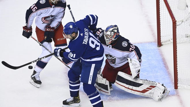 Maple Leafs center John Tavares (91) tries to tip the puck past Blue Jackets goaltender Joonas Korpisalo as Blue Jackets defenseman Dean Kukan watches during a playoff game in Toronto on Sunday, Aug. 2, 2020.
