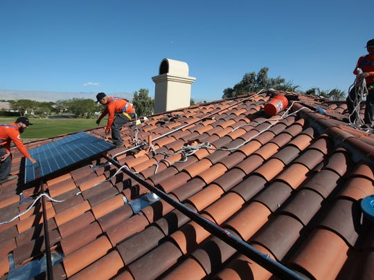 Renova Solar workers install solar panels on a home in the Mission Hills Country Club in Rancho Mirage on Nov. 25, 2015.