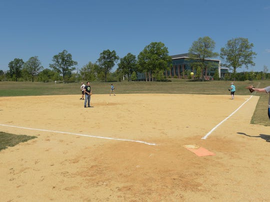 Employees play softball at Commvault's new headquarters in Tinton Falls.