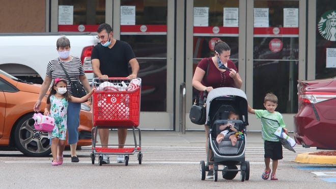 After visiting the Target store in Orange City, some shoppers loosen or remove their face masks as they return to their cars on Wednesday, July 8, 2020. The City Council earlier in the week voted to approve an ordinance mandating masks amid the coronavirus pandemic.