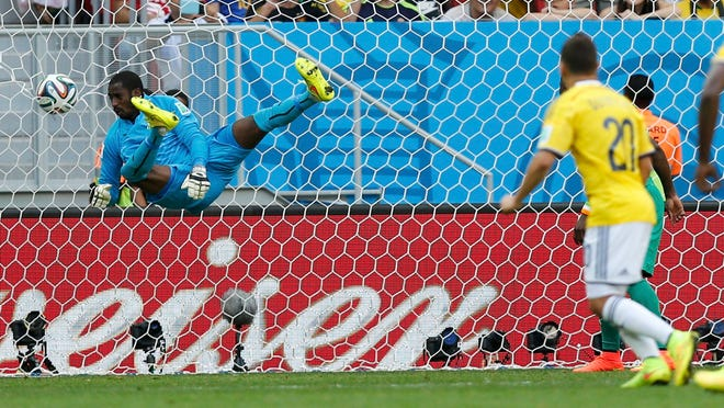 Colombia's Juan Quintero (right) scores past Ivory Coast goalkeeper Boubacar Barry during the second half of a World Cup Group C match Thursday in Brasilia, Brazil.