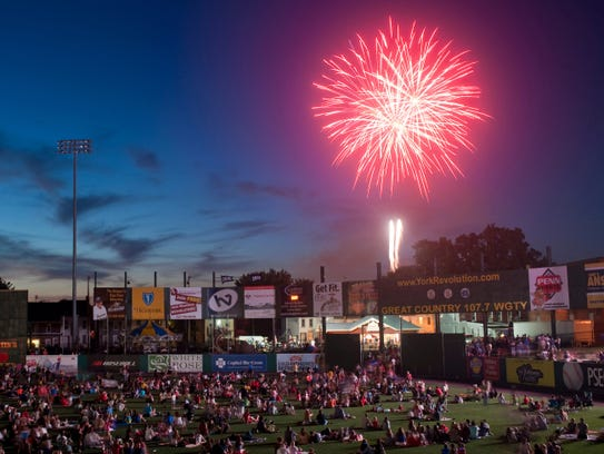 Fireworks explode over the outfield wall during the