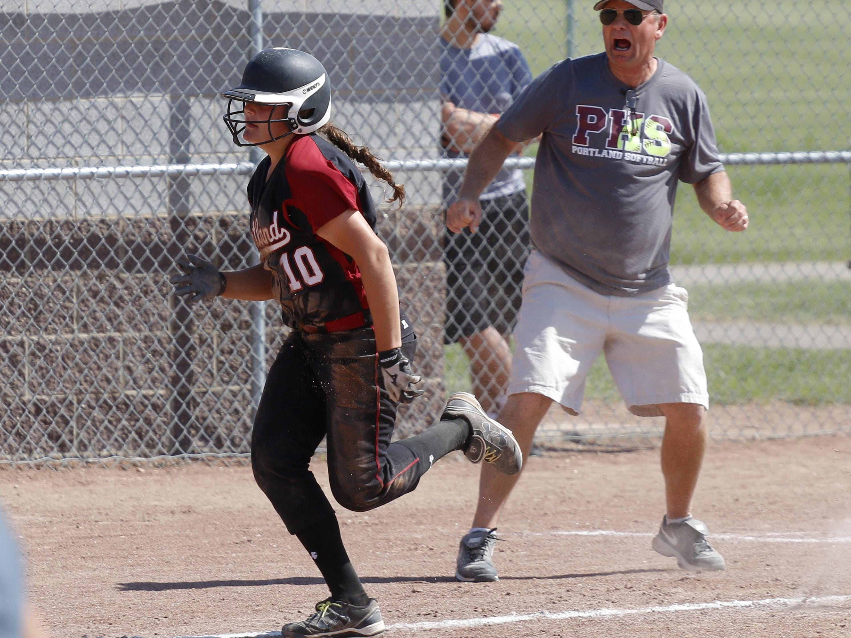 Portland coach Jack Anderson yells encouragement to Olivia Roe as she runs toward home plate during the regional final.