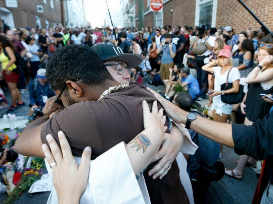 Brittney Cain-Conley, lead organizer for Congregate Charlottesville, with hat, gets a hug from a supporter after she addressed the crowd during a vigil on Sunday, Aug. 13, 2017, held at the site where a car plowed into a crowd of people protesting a white nationalist rally on Saturday in Charlottesville, Va.