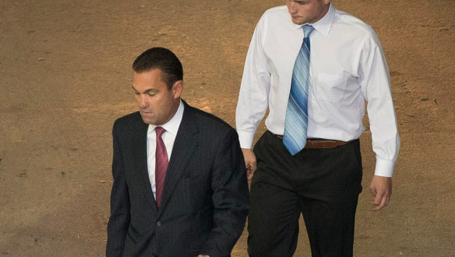 Philip Williams, right, walks to a police station Wednesday, Sept. 24, 2014, in Philadelphia. Williams, Kevin Harrigan and Katherine Knott are being charged with conspiracy, aggravated and simple assault, and reckless endangerment in the Sept. 11 beating of a gay couple during a late-night encounter in Philadelphia.