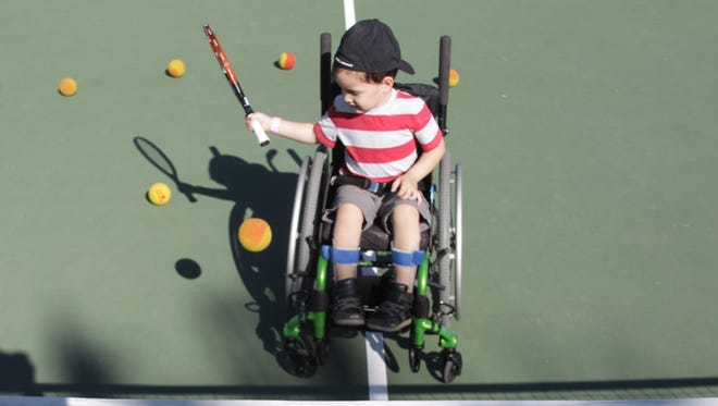 Asher Loera, 4, gets a tennis lesson from instructor Anthony Lara at the Palm Desert Civic Center as part of DisAbility Sports Festival.