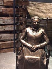 Exhibit and bronze statue that tell the story and life of enslaved individuals. The background of the photo features the Point of Pines Slave Cabin from Edisto, Island South Carolina, that is exhibited in its entire structure.
