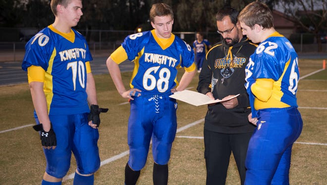 Tempe Prep football players Andrew Stough (70), Connor Woltz (68) and Christian Gaylor (62) huddle around coach Tommy Brittain during a game.