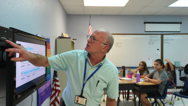 Mountain Home Christian Academy fifth-grade teacher Hubert Pickett sets up a TV Thursday afternoon during a personal finance class named foundations in personal finance. Students watch videos for the first half of the class, and the second half is spent on completing a workbook.