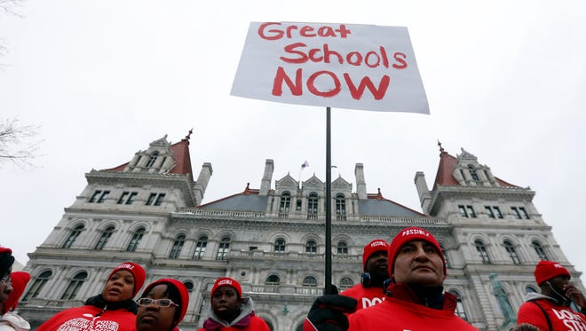 A sign is held during a charter school rally outside the state Capitol on Wednesday, March 4, 2015, in Albany, N.Y.