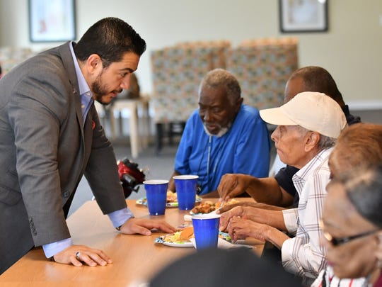 Democratic gubernatorial candidate Abdul Al-Sayed, left, speaks with resident Mary Stroud, right, at the Thome Rivertown Senior Apartments in Detroit on July 12, 2018.