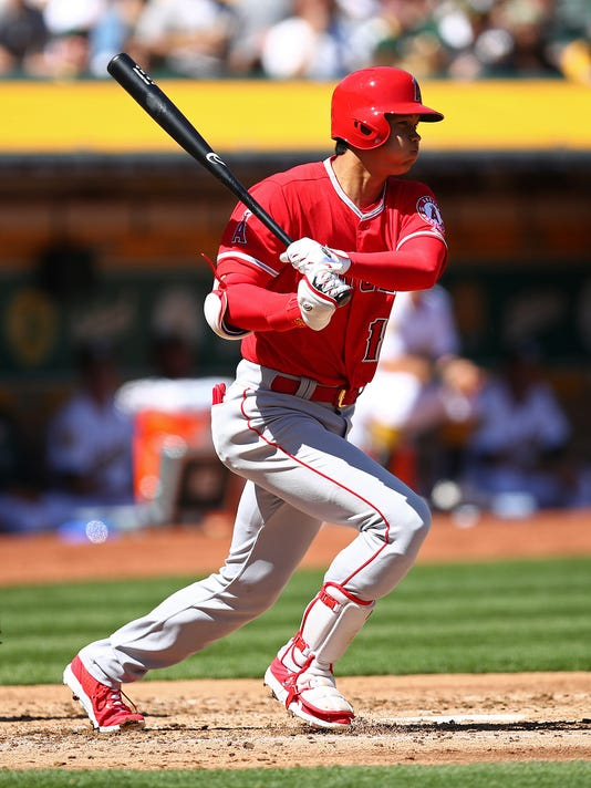 Los Angeles Angels' Shohei Ohtani follows through after hitting a single in his first major league at bat during the second inning of an opening baseball game against the Oakland Athletics, Thursday, March 29, 2018 in Oakland, Calif. (AP Photo/Ben Margot)