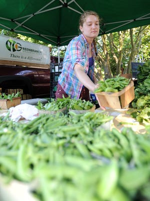 Julianna Brightman of Greenbranch Organic Farm in Salisbury fills a table with peas at the Lewes Historical Complex in Lewes last year.