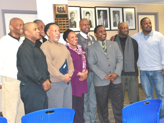 Several recipients of the J. Diann Sams African-American History Month Recognition Award gathered Monday evening in Common Council chambers in Ithaca City Hall for the unveiling of a plaque in honor of Sams, the late member of Common Council. Posing for pictures by friends and relatives are from left, Cal Walker, J.B. Nelson, Sams' son; James Turner; Karl Graham; Marcia Fort; Marlon Byrd; J.R. Clairborne, honored with his wife, Leslyn McBean-Clairborne, not pictured; Abe Lee, honored with wife, Denise, not pictured; Greg Evans, grandson of the late Frances Eastman. Not pictured is the Rev. Ronald Benson.