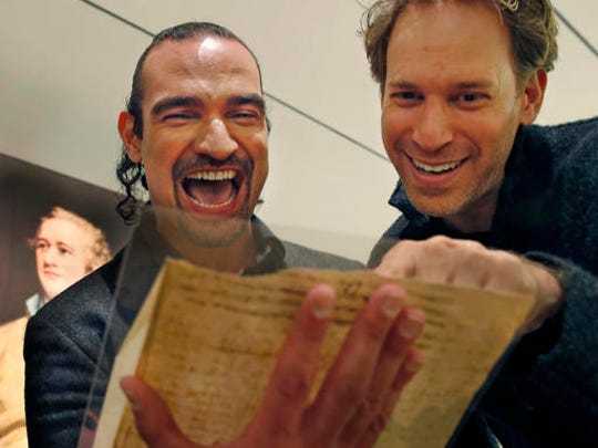"""Javier Munoz, left, who plays Alexander Hamilton in the enormously popular Broadway hip-hop musical """"Hamilton,"""" laughs with the show's set designer David Korins as they read a letter from Hamilton to an unnamed recipient, possibly Jeremiah Wadsworth, about the 1796 presidential election, Tuesday, Jan. 10, 2017, at Sotheby's auction house in New York. This and a trove of artifacts related to Alexander Hamilton, including love letters to his wife, Eliza, will be offered up for auction at Sotheby's Jan. 18, part of """"Americana week."""" Munoz says holding and reading Hamilton's private thoughts about everything from his love life to war in America will have a deep effect on his Broadway performance."""