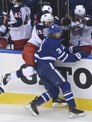 Blue Jackets rookie Liam Foudy is checked into the boards by Maple Leafs defenseman Justin Holl in Sunday night's Game 5. Foudy got a tooth chipped in the game, but also scored his first NHL goal.