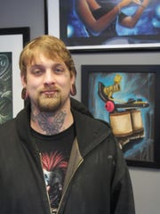 Kyle Leusink, with his painting of a tattoo gun behind