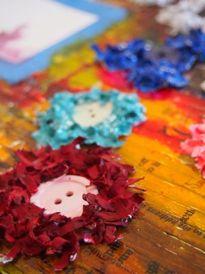 Using shredded paper, Schommer decorates a collage with paper flowers.
