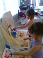 Jazlyn and Kalyn Hubble create abstract paintings.