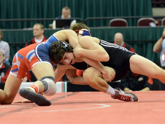 Genoa's Damian D'Emilio, right, wrestles Haviland Wayne