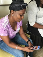 """In this Sunday, June, 12, 2016 file photo, Wilhemina Justice looks at a photo of her son, Eddie Justice, who was killed in the Pulse nightclub mass shooting, as she speaks to a reporter in Orlando, Fla. In the wake of his death, a friend of Eddie and another man set up a GoFundMe charity page in his memory, saying the money would pay for his funeral and victim counseling. But Justice's mother said no one consulted her about the appeal in her son's name or made arrangements to give her proceeds. """"To me, it's fraud,"""" she said."""