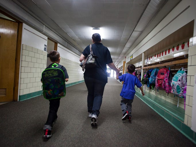 Jaime Sanchez from Cedar City walks her boys to class on the first day of school at East Elementary on Thursday August 14, 2014.