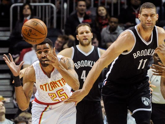 Atlanta Hawks forward Thabo Sefolosha (25), of Switzerland, comes up with the ball as Brooklyn Nets center Brook Lopez (11) tries to keep him from it during the first half of an NBA basketball game, Saturday, Jan. 16, 2016, in Atlanta. (AP Photo/John Amis)
