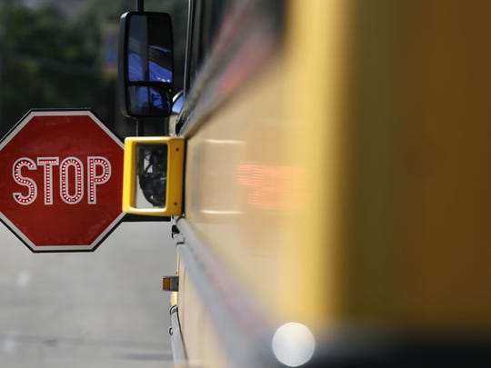 A camera sits mounted next to a school bus stop sign.