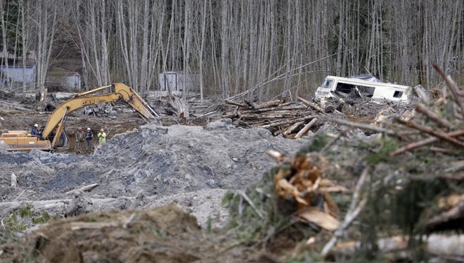 A demolished recreational vehicle lies in a debris field at the scene of a deadly mudslide nearly two weeks earlier nearby, Thursday, April 3, 2014, in Oso, Wash. More than a dozen people are listed as missing and 30 bodies have been found in debris from the March 22 landslide that broke off a steep hill, roared across the North Fork of the Stillaguamish River and buried a community at Oso, about 55 miles north of Seattle. (AP Photo/Elaine Thompson)