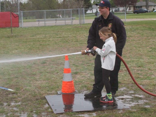 Jalyn Ray, 7, takes her turn on the water hose from