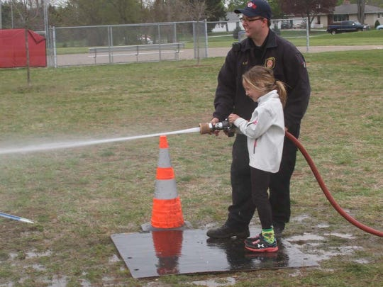 Jalyn Ray, 7, takes her turn on the water hose from a Hamburg Township fire truck during Country Elementary School's annual fire safety day.