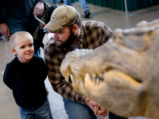 In this file photo, Eli Roberts, 3, and his father, Zack, of Frostburg, Maryland checkout an alligator at the Wildlife Studios booth at the Great American Outdoor Show on Thursday, February 12, 2015.