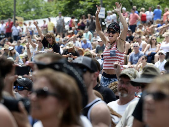 A spectator dances as she listens to Kristian Bush