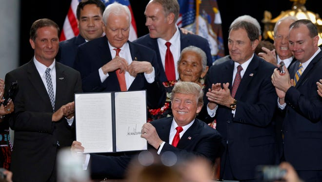 President Donald Trump holds up a signed proclamation to shrink the size of Bears Ears and Grand Staircase Escalante national monuments at the Utah State Capitol Monday, Dec. 4, 2017, in Salt Lake City. Trump traveled to Salt Lake City to announce plans to shrink two sprawling national monuments in Utah in a move that will delight the state's GOP politicians and many rural residents who see the lands as prime examples of federal overreach, but will enrage tribes and environmentalist groups who vow to immediately sue to preserve the monuments.