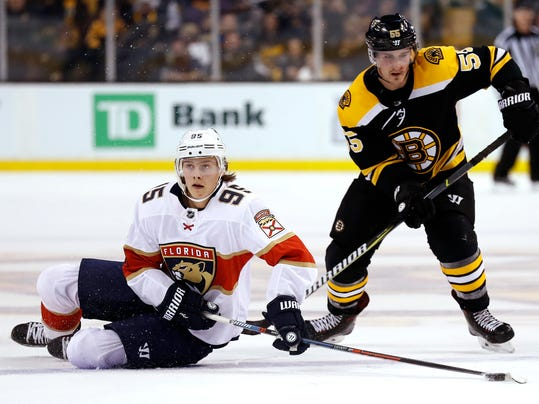 Florida Panthers' Henrik Borgstrom tries to control the puck from the ice as Boston Bruins' Noel Acciari moves in during the second period of an NHL hockey game in Boston Sunday, April 8, 2018. (AP Photo/Winslow Townson)