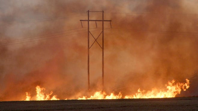 A line of fire catches power poles on fire as it burns a field of uncut wheat north of Pratt on U.S. Highway 281 between NW 20th Street and NW 30th Street on Wednesday, June 24. Several lightning strikes from a storm over Kiowa and Edwards counties hit around 7:32 p.m. and ignited this fire. Other fires in neighboring counties were also caused by lightning from the storm.